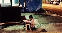 Obdachloser Junge lernt im Lichtschein vor einer McDonald's Filiale