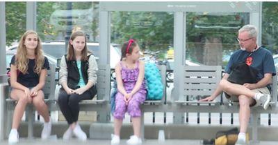 Zwei Freundinnen mobben ein jüngeres Mädchen an einer Bushaltestelle